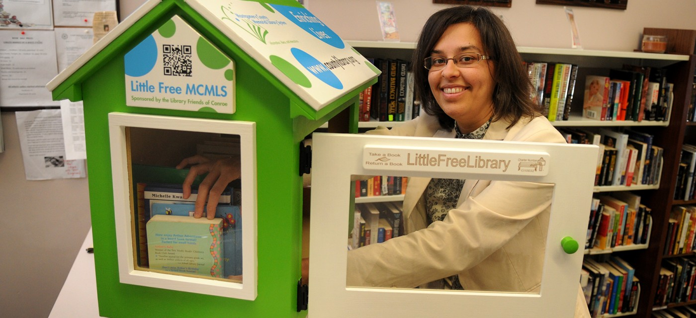 Melissa Baker, Marketing and Program Coordinator for the Montgomery County Memorial Library System, loads up the new Little Free Library at the CentralLibrary in Conroe.