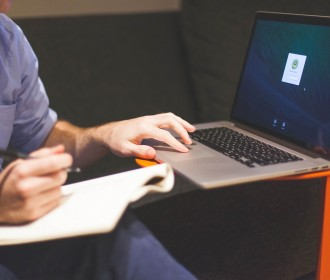 Man with notebook and hand on a laptop