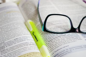 glasses on a book with a highlighter