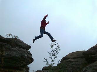 man leaping across a cliff