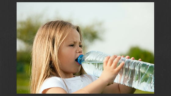 girl drinking a bottle of water