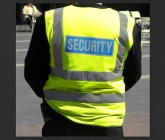 back of a person in yellow jacket with security written on it