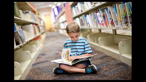 kid reading book on floor in library between rows of library shelves
