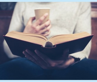 person holding a book and a cup of coffee
