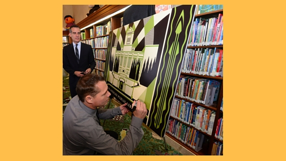 Los Angeles Mayor Eric Garcetti (left) watches artist Shepard Fairey sign a replica of LA's first artist-designed, limited-edition library card at the press launch on April 19 at the Central Library. The card is available at all 73 locations of the Los Angeles Public Library.