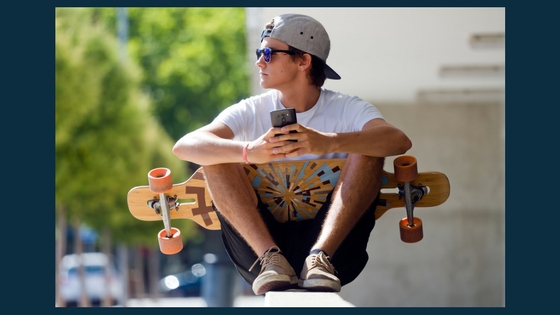 teenager holding a phone and a skateboard