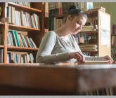 person reading in library at desk in front of book shelves