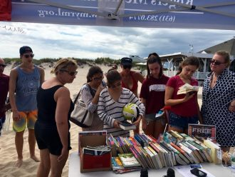Beach goers browse through books at the Pop Up Library. Photo Courtesy of Rogers Memorial Library