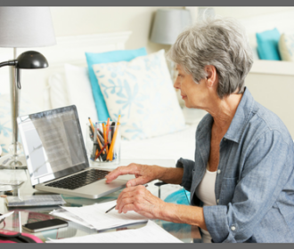woman with gray hair working at a computer