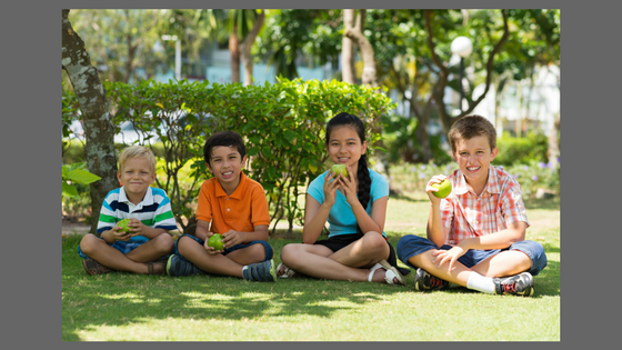 kids sitting on a lawn eating apples