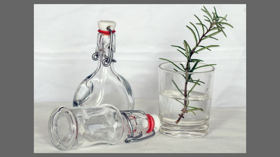 decorative bottles, a glass, a sprig of rosemary