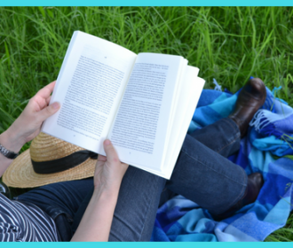 person reading in on a blanket in grass with straw hat on lap