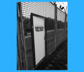 Fence with door that says Refugees Welcome