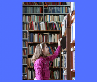Photo of a child pulling a book from a shelf in a library