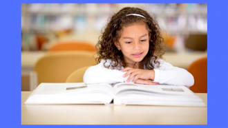 photograph of a girl in a library setting reading a large book