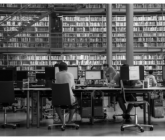 black adn white photo of people working on computers at a library