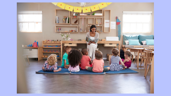 adult reading to gathered children photo