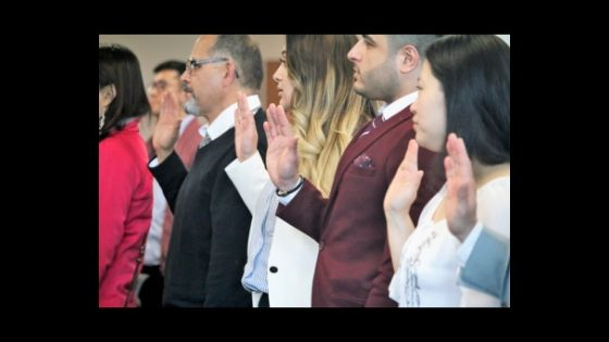 Group of people taking citizenship oath