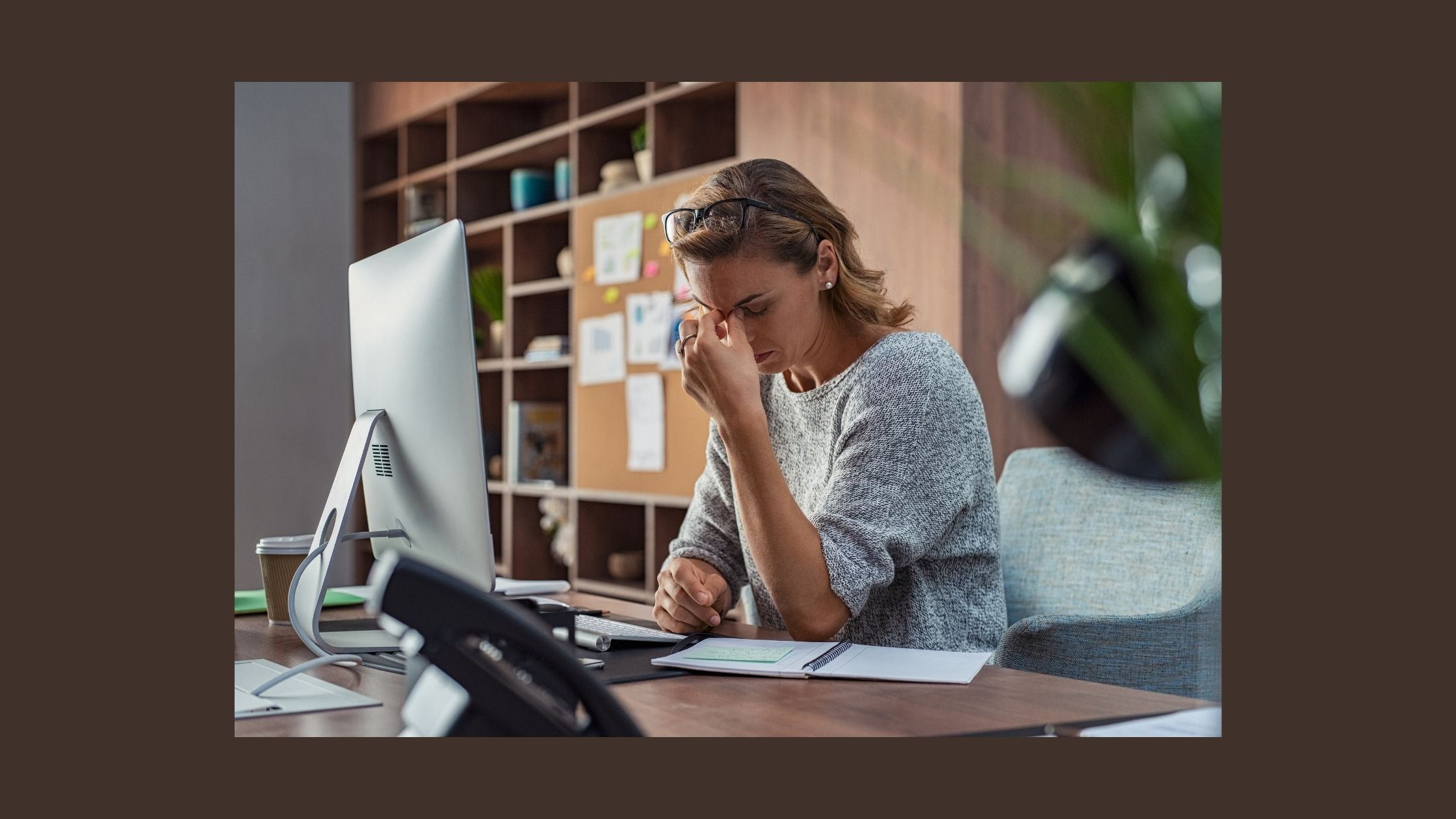 person at desk looking tired and overwhelmed