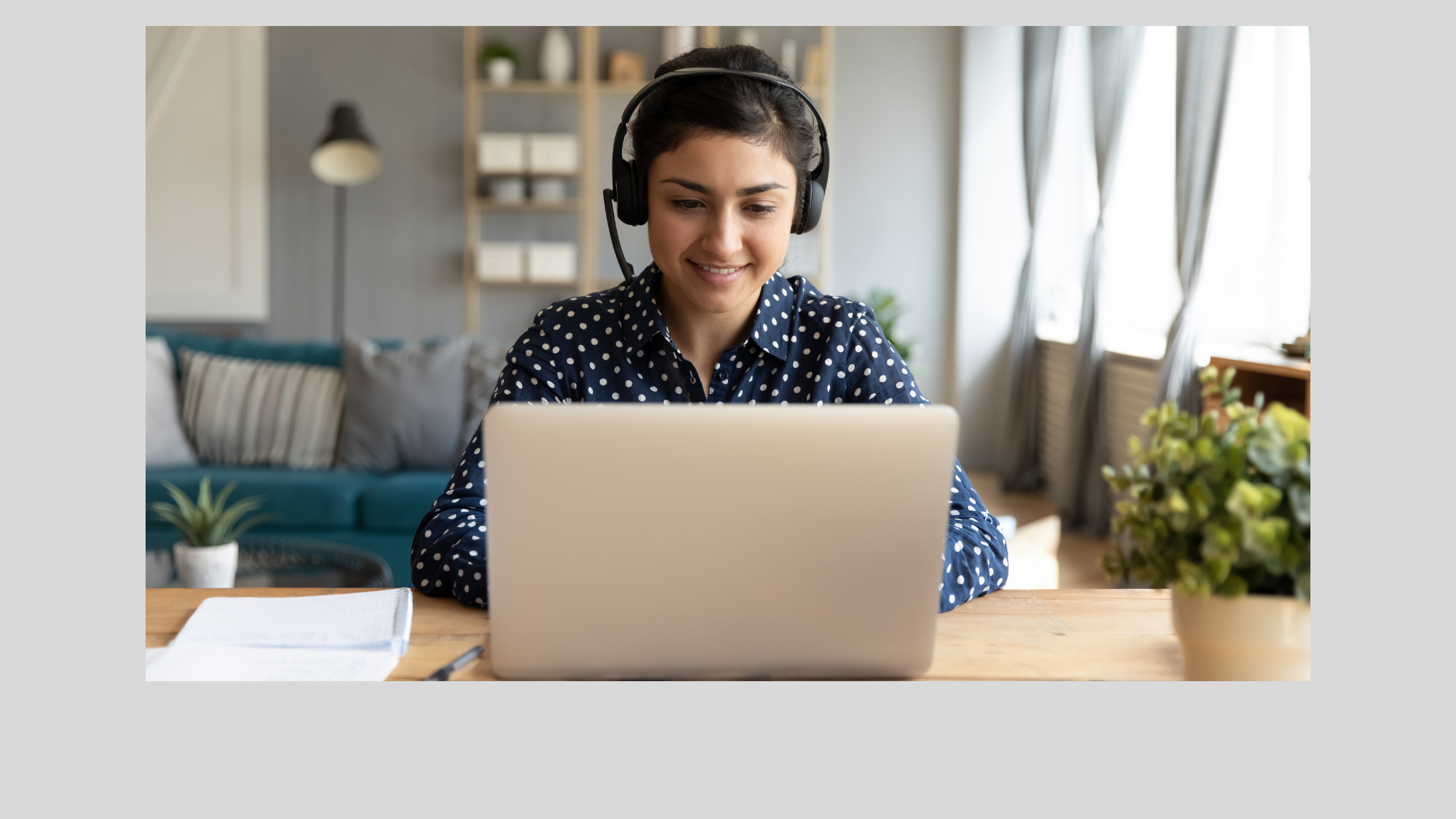 photo of a woman at a laptop with headphones